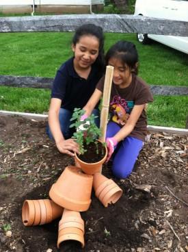 """Alicia Galindo and Crystal Rafael assemble """"Clay Pot Man""""."""