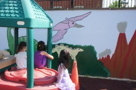 Children attending the daycare housed at the Nutritional Sciences Preschool facility, admire the new mural on the playground.