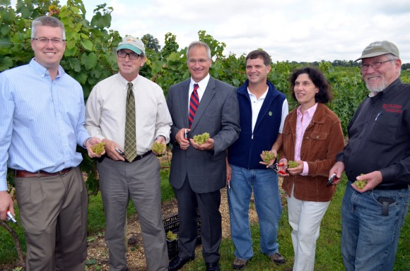 New Jersey Secretary of Agriculture Douglas H. Fisher visited Working Dog Winery in East Windsor on September 16 to announce the beginning of Wine Week in New Jersey, celebrating the Garden State's 2014 grape harvest. Joining him to kick off NJ Wine Week are (l-r) Larry Sharrott, Chairman of the Garden State Wine Growers Assoc.; Secretary Fisher; Alcoholic Beverage Control Dir. Michael Halfacre; Mark Carduner of Working Dog Winery; East Windsor Mayor Janice Mironov; and Rutgers School of Environmental and Biological Sciences Executive Dean Robert Goodman. Source: NJDA