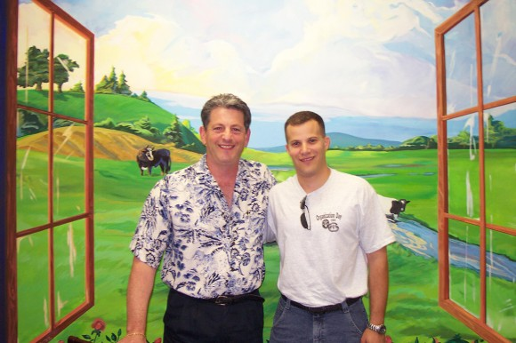 Scott Willens, right, poses with his former G.H. Honors advisor Larry Katz in front of a pastoral mural, painted by Hedy McDonald, a Katz family friend.
