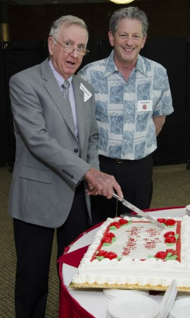 Former and current Rutgers Cooperative Extension directors John Gerwig (left) and Larry Katz cut the cake at the Rutgers retirees event commemorating the 100th anniversary of Cooperative Extension.