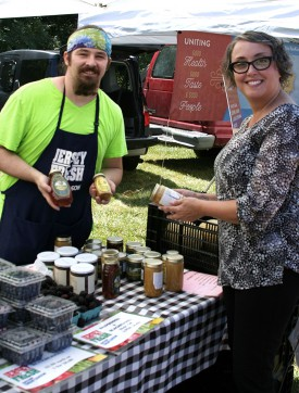 Dalynn Knigge, who administers OCPE's Bee-ginner's Beekeeping course, and Nick Kallatch display locally harvested honey sold by Fruitwood Orchards, a weekly vendor at the Rutgers Gardens Farmers Market.