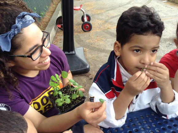 New Jersey FoodCorps member Thalya Reyes and New Brunswick pre-schooler Julio, savoring the fragrance of fresh basil at New Brunswick Community Farmers Market.