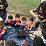 Thalya gives pre-schoolers a hands-on demonstration of planting seeds.