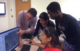 Prof. David Tulloch points to an image on the screen. On his left are workshop participants Sree Thogarchedu, Agurami Agbeyegbe and Tara Viray.