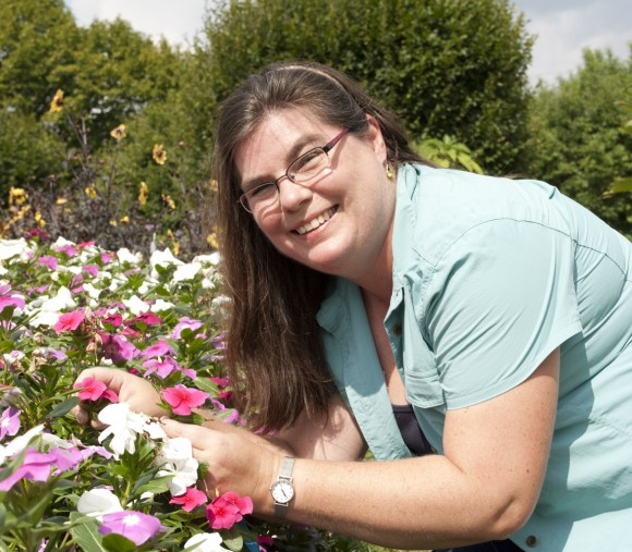 Lena Struwe demonstrates rosy periwinkle (Catharanthus roseus), the source of the anti-cancer compound vincristine, at the Rutgers Gardens. Photo by Susanne Ruemmele.
