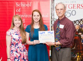 Students Nicole Tallman (l) and Sarah Waxman present dean Rick Ludescher with the Teacher of the Year Award.