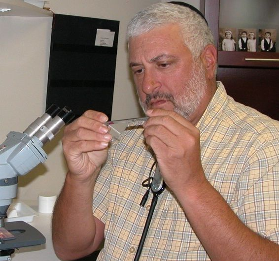 Dr. Leonard Bielory at microscope.