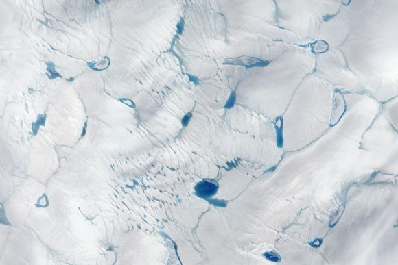 Early melting, featuring a melt pond, on the Greenland Ice Sheet on June 15, 2016. Photo: NASA Earth Observatory