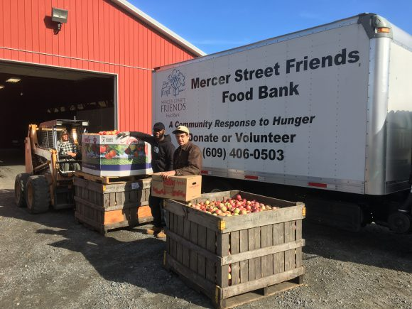 Snyder Farm staff member Curtis McKittrick (r) assists Mercer Street Freinds Food Bank in getting a load of apples onto their truck.