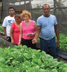 The Sookraj family of Pouderoyen, West Bank Demerara, Region 3, Guyana, admire shade house bok choy grown by the family. Kelvin Craig, standing in front, joins Robin Brumfield, with notepad, on a Suzanne's Project operation. Photo: Paula Quintin, Rutgers University.
